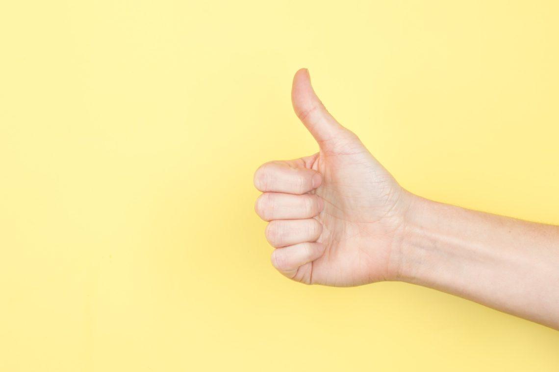 Thumbs up on yellow photo by Sarah Pflug