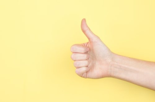 Thumbs up on yellow photo by Sarah Pflug
